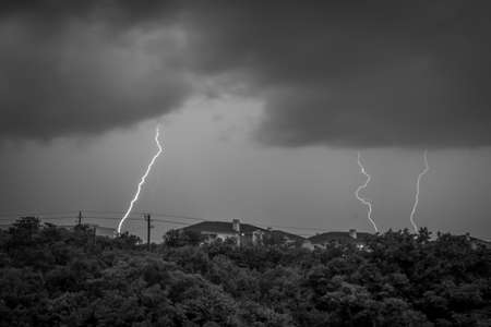Black & White Nature Photo of Bolts of Lightning Striking a Suburban Neighborhood - with Houses, Trees and Powerlines on a Dark and Stormy Night Фото со стока