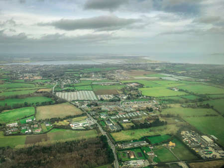 Aerial Flyover View of the Western Countryside of Ireland - with Green Pastures and Cloudy Skies Banco de Imagens