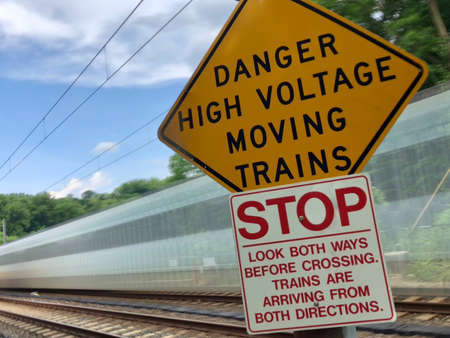 Colorful, Long Exposure Photo of a Blurry Train Speeding Behind a Pair of Caution Signs, with a Bright Blue Sky and Green Trees in the Background