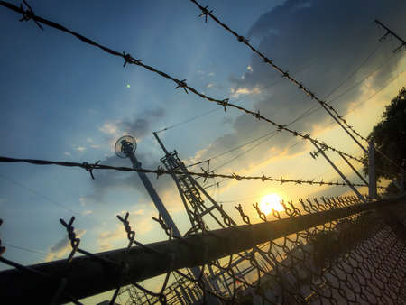Angled Photo of a Barbed Wire Fence and Electrical Station at Sunset - in a Southwest American Town with a Striking Blue and Yellow Sunset in the Background