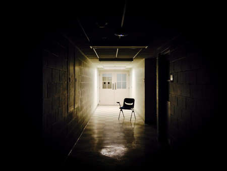 Moody, Shadowy Photo of an Isolated School Chair - Placed at the End of a Dark, Empty Hallway with a Single Source of Light in the Background