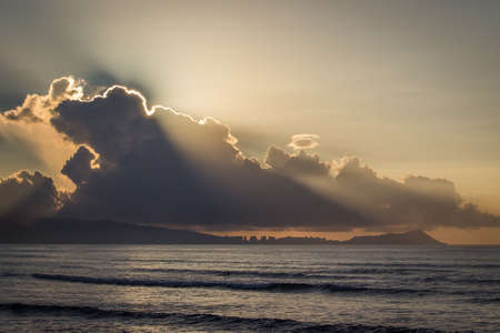 Ocean on a Cloudy Sunrise - with Rays of Sun Shining Around the Edge of the Clouds on the Horizon, and Calm, Empty Waves Below on a Summer Morning in Hawaii Banco de Imagens