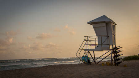 Photo of a Tropical Beach Lifeguard Station at Sunset - with a Smooth Sky, Light Clouds and Cresting Waves in the Background