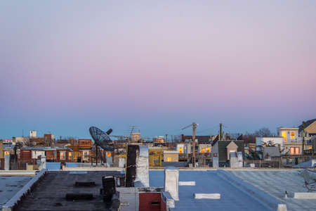 Vista of City Rooftops at Sunset - with a Sprawl of Row Houses and Rooftop Porches Under a Smooth, Pink and Blue Cloudless Sky