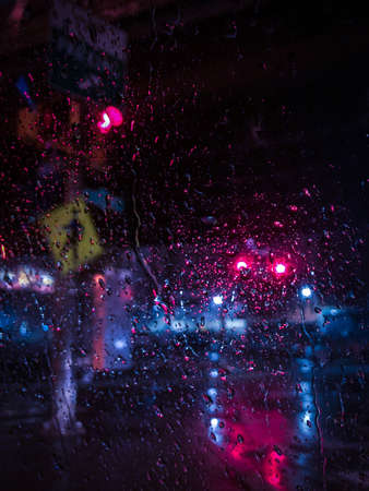 Raindrops Covering a Window, Looking Outside a City Street at Night with a Stop Light and Passing Car in the Background Banco de Imagens