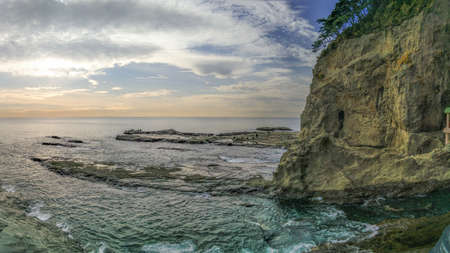 Panorama Photo of a Seaside Cliff on a Cloudy Day - with Shallow Water Crashing Against Rocks, and a Patch of Trees Overlooking the Top of the Cliff on the Southeast Coast of Japan