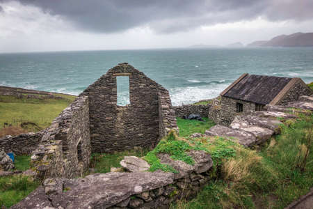 Landscape Shot of Old House Ruins Along the Coast of Ireland - with Cloudy Skies and Blue Ocean in the Background