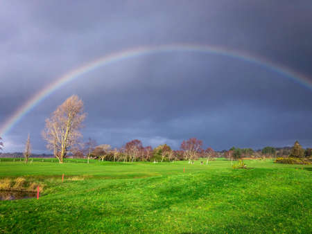 Landscape Shot of a Rainbow Shining Above a Golf Course During a Cloudy, Overcast Day