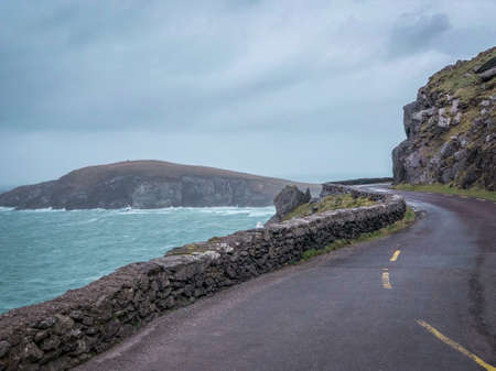 Landscape Shot of a Winding Road Overlooking the Southern Coast of Ireland on an Overcast Day - with Clear Blue Water and an Island in the Background Banco de Imagens