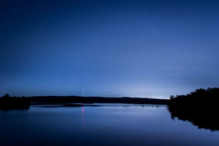 Star Trail Photo of Stars Above a Lake at Night - with Specks of Starlight in the Sky, Smooth Reflective Water, and Trees, Hills and a Red Beacon Light in the Background on a Clear Night in the Woods Banco de Imagens