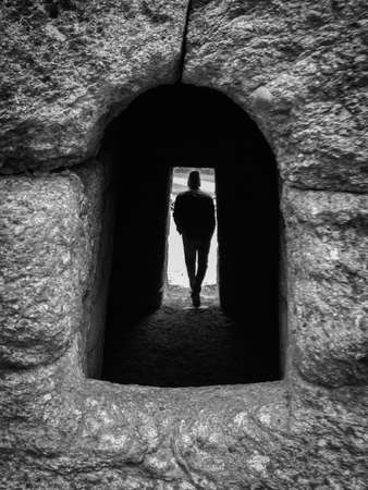 Shadowy, Black & White Silhouette of a Young Man Standing in an Archway - Shot Through a Stone Window