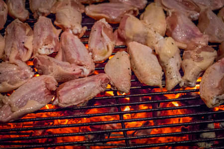 Close-Up Shot of Raw Chicken Wings as They are Being Cooked on a Flaming Hot Barbeque Grill