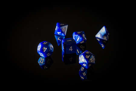 Moody, Shadowy Photo of Six Blue Role Playing Gaming Dice Displayed on a Reflective Surface, with a Dark Black Background Banco de Imagens
