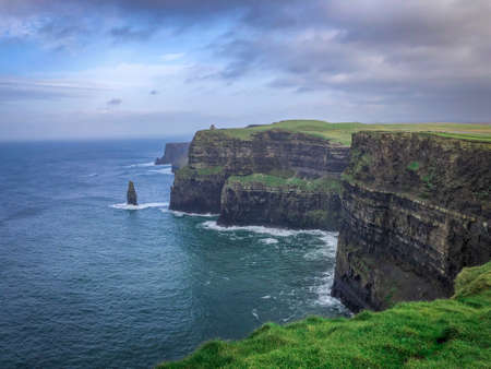 Landscape Shot of the Cliffs of Moher in Ireland - on a Cold Winter Day with Green Grass, Cragged Rocks, Bright Blue water and Cloudy Skies Overhead Banco de Imagens