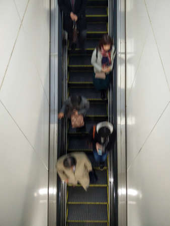 Top-Down Aerial View of Men and Women Riding Down the Escalator in the Business District of a Major City