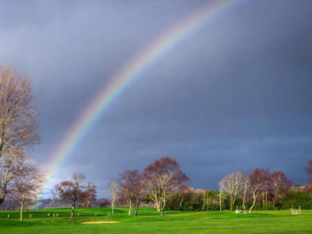 Shot of the Tail End of a Rainbow Shining Above a Golf Course During a Cloudy, Overcast Day Banco de Imagens