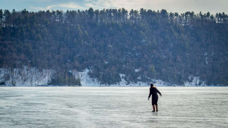 Woman in Black Walking on Top of a Frozen Lake - with a Hill and Trees in the Background on a Cold, Winter Day