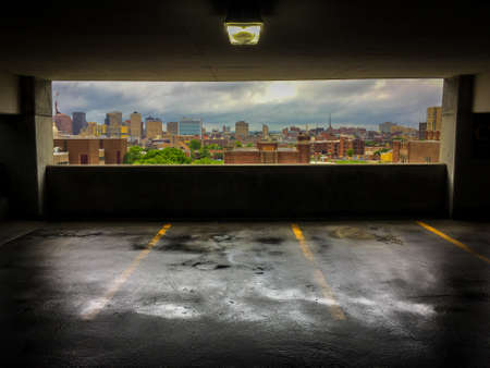 Colorful Photo of a View of the City of Baltimore from a Parking Garage - with a Wet, Rain Slick Floor and a Cloudy Blue Sky Over the Skyline in the Background