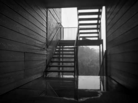 Black & White Photo of a Staircase in the Wet Alley of a Housing Complex - with Rain Slick Walls, and Puddles on the Ground After a Heavy Summer Storm