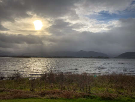 Landscape Shot of a Lake in Ireland on a Winter Morning - with the Sun Shining Through Clouds in the Background