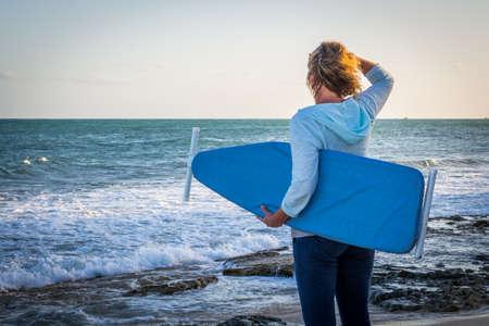 Colorful, Funny, Photo of a Brown Haired Woman Looking Out to the Ocean while Holding an Ironing Board - with Crashing Waves and Rocks on a Warm Morning