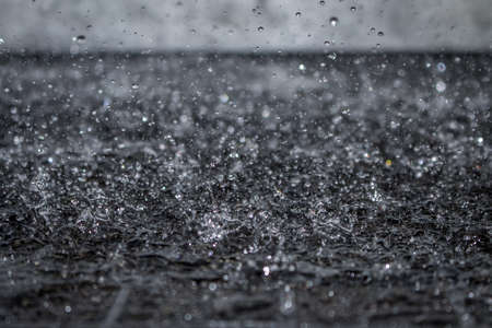Close Up Macro Photo of Water Drops Falling and Splashing on Black Tile - with Droplets Frozen in Mid Air