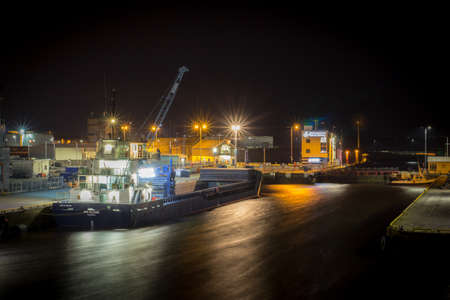 Freighter Docked in a Shipyard, as Materials are Loaded into the Hull by a Crane - Shot at Night Banco de Imagens