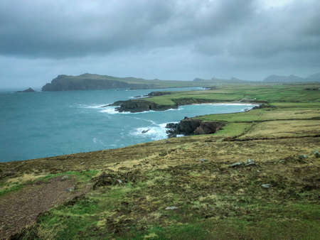 Landscape Shot Overlooking the Coast of Southern Ireland off the Dingle Peninsula - on a Cold Winter Day with Bright Blue Waters and Cloudy Skies in the Background Banco de Imagens