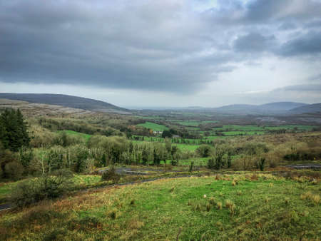 Landscape Shot Overlooking the Countryside in Southern Ireland - Taken Above a Long, Winding Road, with Pastures, Mountains and a Cloudy Sky in the Background