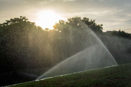 Water Sprinklers at Sunset - with a Fine Mist of Water in the Air and the Sun Setting Over Trees in the Background