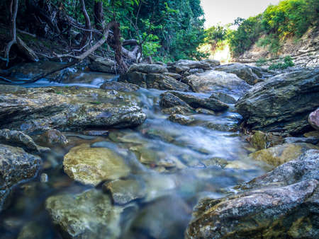Long Exposure Close Up Photo of Water Streaming Through Rocks in a Shallow Creek - with Trees and a Valley in the Background on a Bright Summer Day in Central Texas