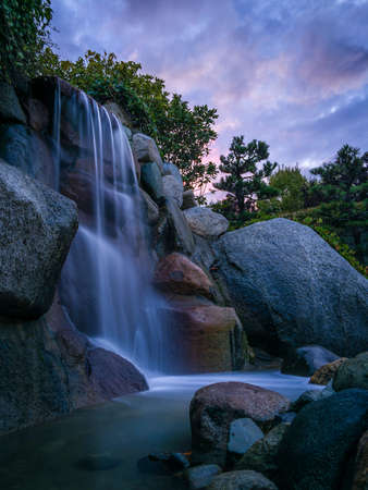 Vibrant, Long Exposure Photo of a Waterfall at Sunset - with Water Cascading Over Rocks, and a Purple and Pink Sky in the Background Banco de Imagens