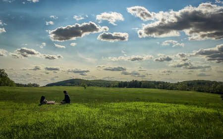 Vibrant Photo of Two People Picnicking in a Field on a Sunny Day - with Green Grass, Blue Skies and Spots of Clouds at a Park in the Mid Atlantic United States