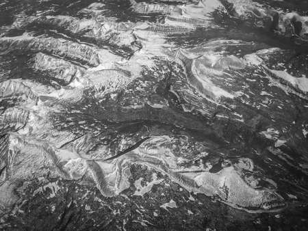 Black & White High Altitude Aerial Photo of Snow Covered Mountain Ridges in the Winter - with Curving Peaks and Troughs on a Bright, Clear, Sunny Day