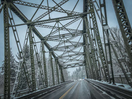 Angled Photo of a Bridge and Wet Road, with Snow Covered Trees in the Background on a Cold, Winter Day in the Pacific Northwest