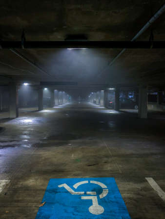 Moody Photo of a Handicap Spot in a Parking Garage on a Rainy Night, with Heavy Fog in and Rays of Light in the Background