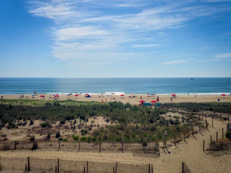 Aerial Drone Photo of a Mid Atlantic Beach on a Sunny Afternoon - with Sand Dunes and People on the Beach, and Smooth Ocean Water in the Distance Banco de Imagens