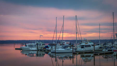 Boats at a Dock at Sunset - with Smooth, Reflective Water During a Pink Cloudy Sunset