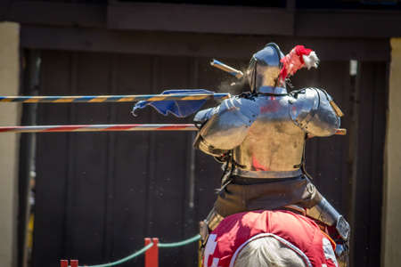 Close Up Action Photo of an Armored Jouster on a Horse - Getting Hit in the Chest by a Broken Jousting Pole During a Duel at a Medieval Fair