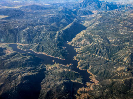 High Altitude Aerial Photo of Mountains, Hills and a River - with Rigid Peaks, Green Vegetation and Rocky Geography in the Western United States on a Bright, Hazy Day Banco de Imagens