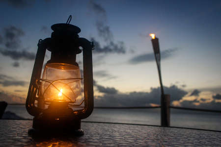 Close Up Photo of a Gas Lantern on a Table - in the Caribbean at Dusk with a Tiki Torch and the Ocean in the Background