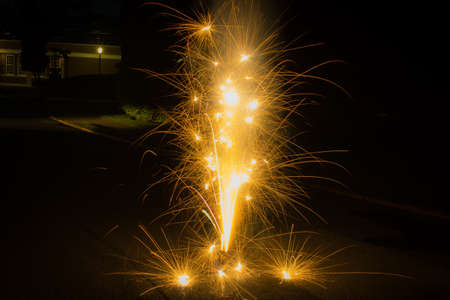 Long Exposure Action Photo of Gold Fireworks Exploding on the Ground - with Streaks of Embers Shooting in Multiple Directions in a Suburban Neighborhood During the 4th of July