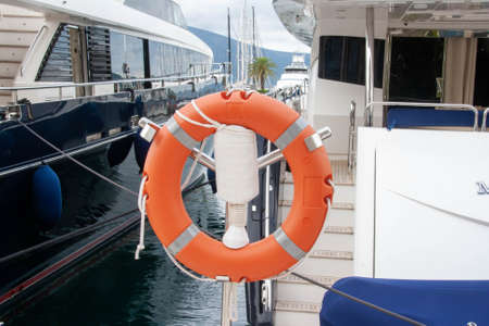 Lifebuoy or life ring orange with a backdrop of the sea landscape. Safety equipment. High-quality stock photo image of obligatory ship equipment, personal flotation device prevent drowning Stock fotó - 131236947