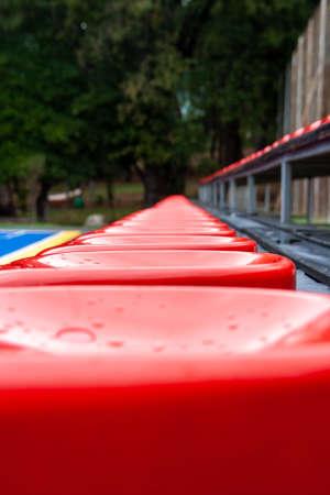Rows of empty plastic stadium red seats