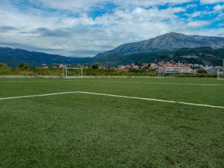 On the football field. Behind the goal of a soccer field. Soccer football net background over green grass or soccer field and blurry stadium and soccer players. Фото со стока - 146903340