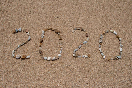 The message Year 2020 written on beach wet sand background. Can use for Happy new year 2020