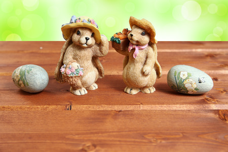 Two Easter bunny on wood background with decorative eggs