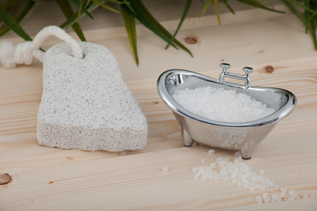 Natural bath salt, organic products placed on wooden background with spa accessories.