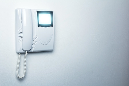 interphone: a video entryphone turned on on a white wall Stock Photo