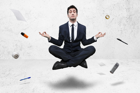 young businessman meditating in yoga lotus pose